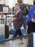 Reese Witherspoon rested a hand on her baby bump as she walked through LAX.