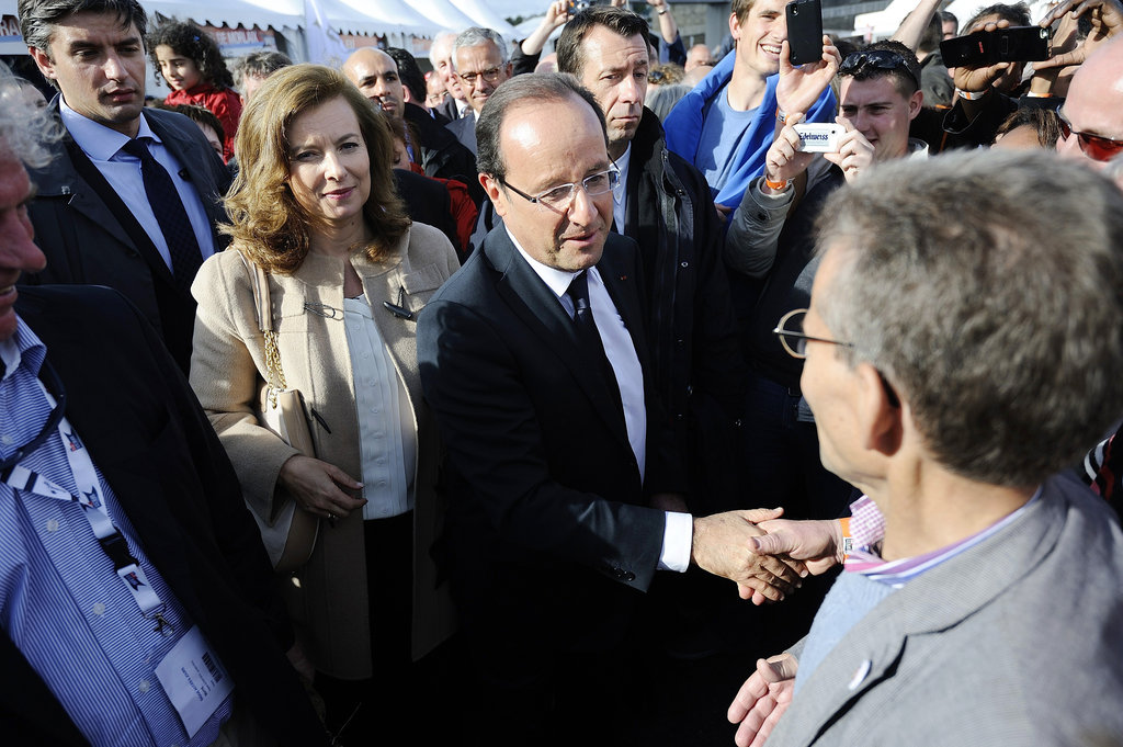 French president François Hollande shook hands with someone with his partner Valérie Trierweiler beside him.