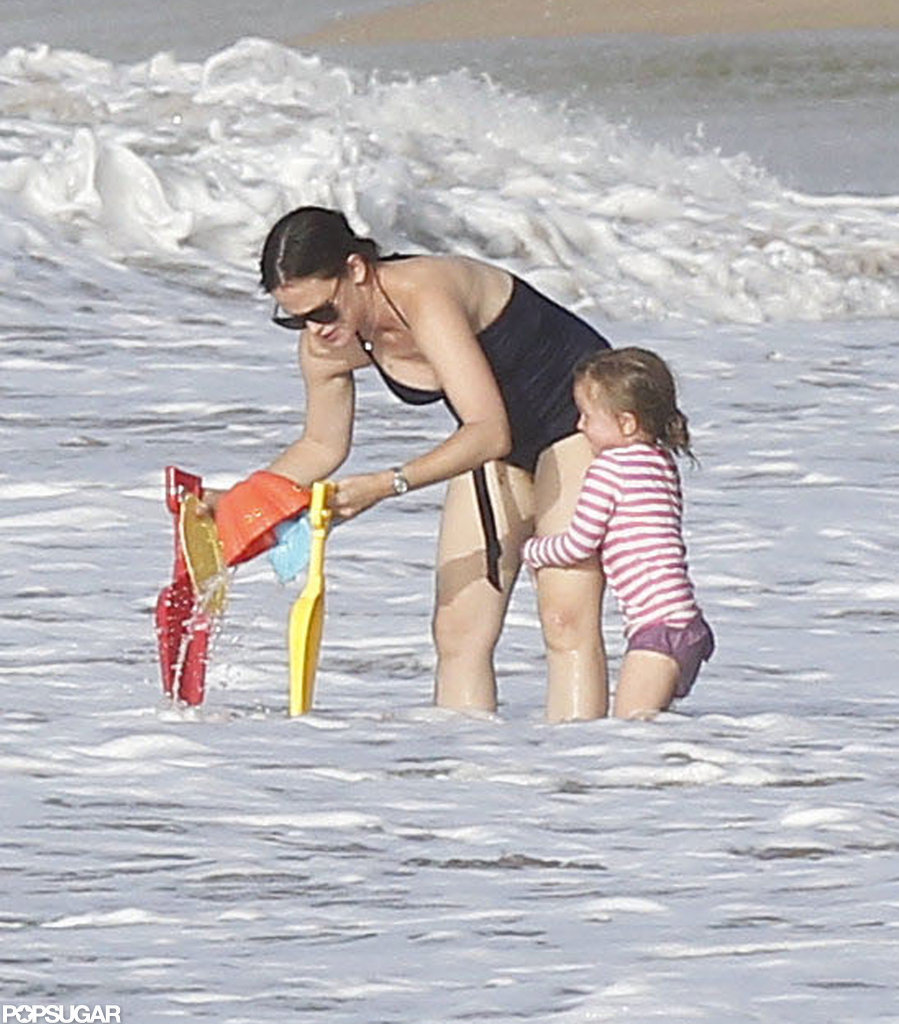 Jennifer Garner rinsed off the beach toys while Seraphina held onto her leg.