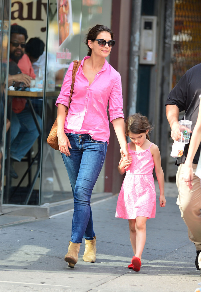 Katie Holmes punched up a pair of blue jeans with a neon button-down while out with Suri around NYC.