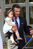 David Beckham held Harper Beckham in her white dress.