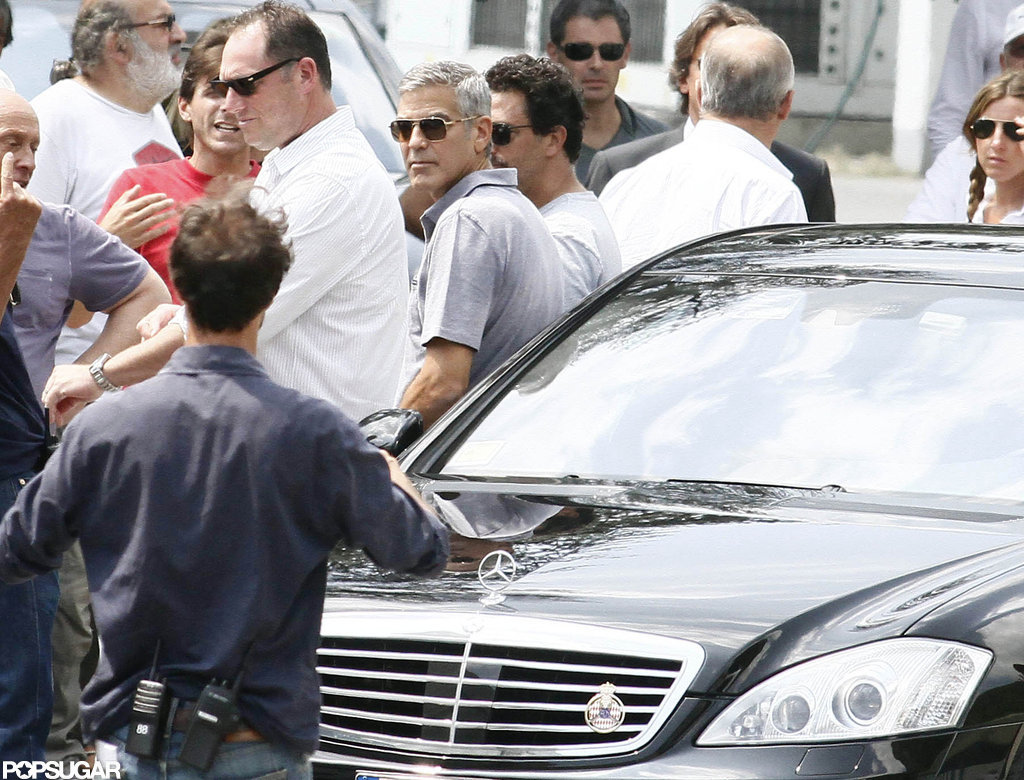 George Clooney and the crew gathered around a black Mercedes.