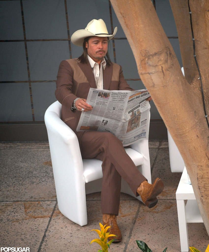 Brad Pitt read the paper while on the set of his latest film.