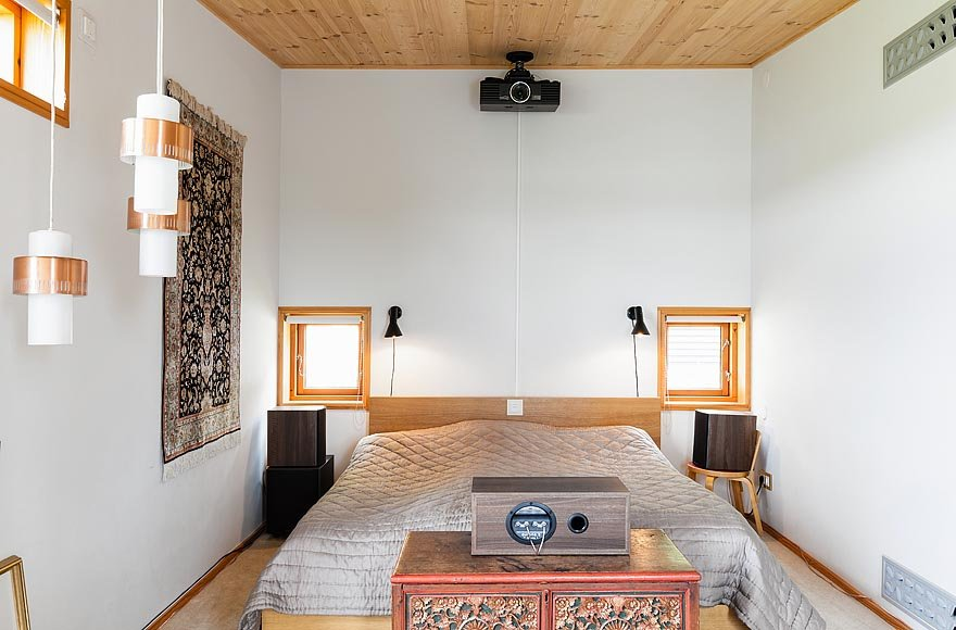 Wood paneled ceilings and simple white walls are featured in one of the bedrooms.