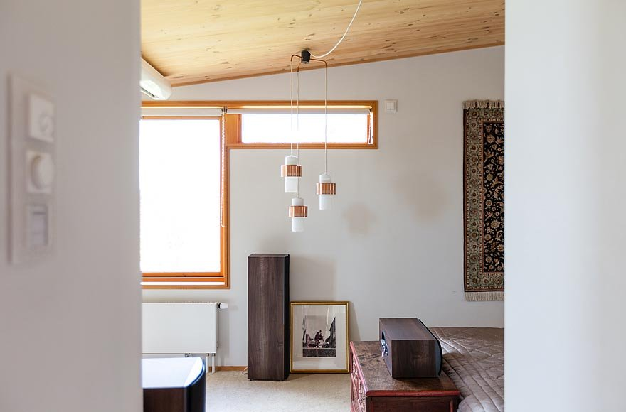 A trio of pendants in one of the bedrooms hang in front of two windows.