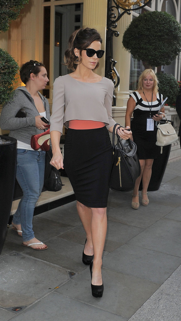 While strutting her svelte stuff in London, Kate sported a chic colorblock Paule Ka look: gray cropped top, black pencil skirt, coral belt, black suede platform Brian Atwood pumps ($754), these gold spiked Melinda Maria earrings ($80), finished with cat-eye shades, and this Alexander McQueen bag ($2,995).   8310384