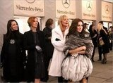 She layered herself in a plush white fur overcoat and black driving gloves for a Fashion Week appearance.