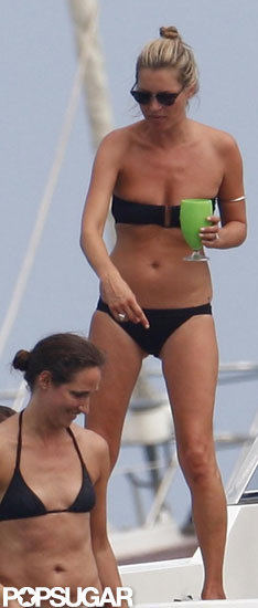 Kate Moss held a glass while on a boat in her bikini.