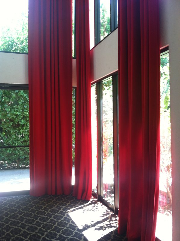 A stroll through the North Building's hallways reveals soaring ceilings paired with tall windows and dramatic red drapes.