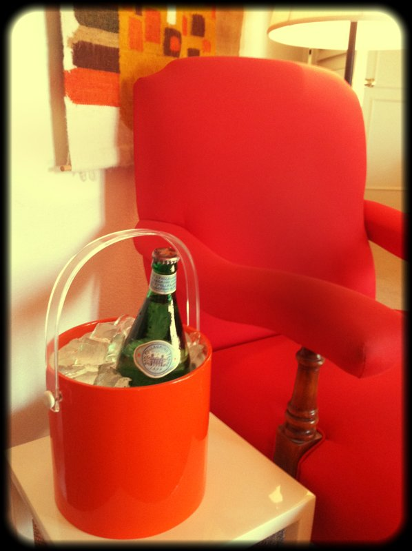 A bright red chair with lengthy armrests sits in another corner of the room.