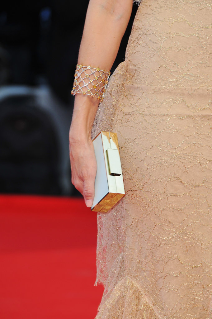 She carries a slick white and gold Lanvin clutch.