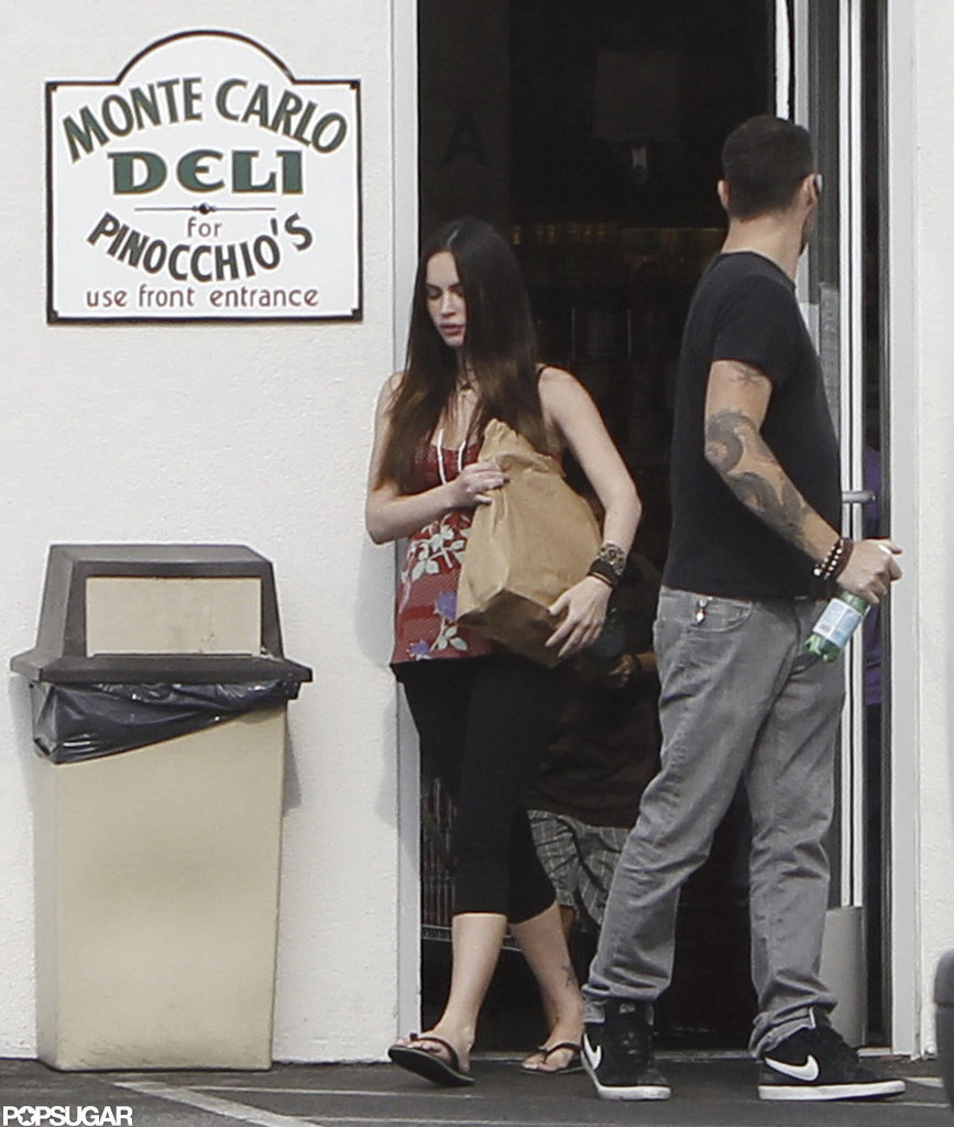Pregnant Megan Fox carried food out of a deli while Brian Austin Green held the door.