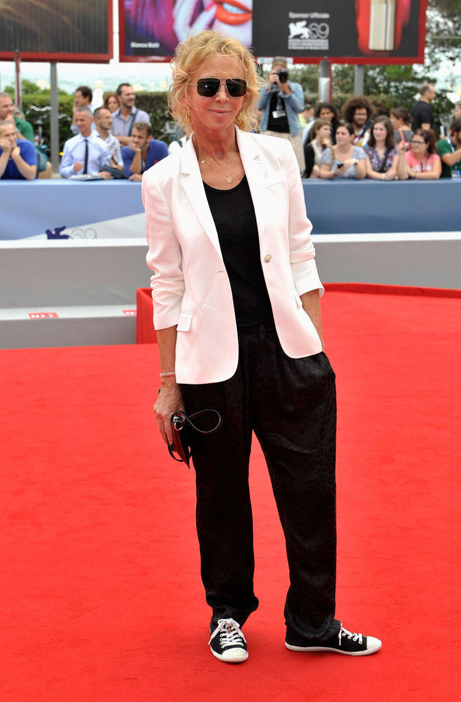 Sting's wife, Trudie Styler, surprised in a black jumpsuit, white blazer, and low-top sneaker outfit.