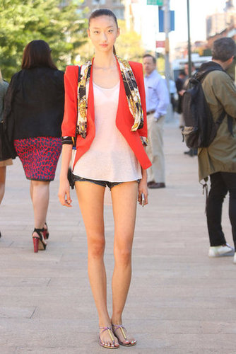 Just a printed silk scarf and a bright coral jacket lend a touch of ladylike polish to cutoffs and a tank. Source: Greg Kessler