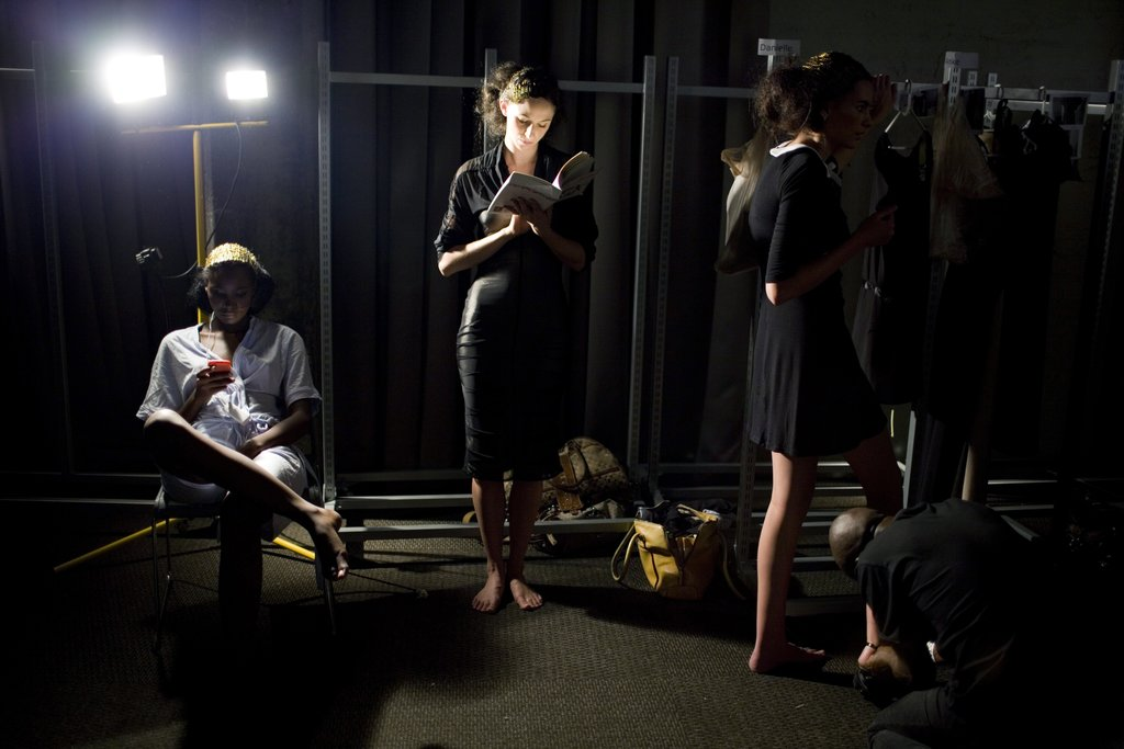 A model found a spot of light to read her book backstage during Fashion Week in South Africa.