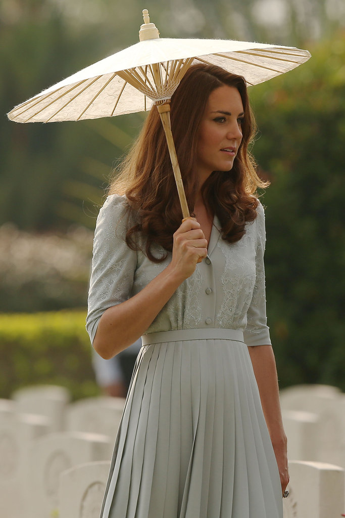 Earlier in the day, Kate teamed the buttons and lace front and pleated knee-length skirt cinched in at the waist with a parasol for a tour of the Kranji War Memorial in Singapore.