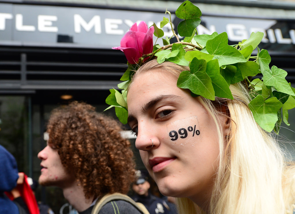 "A woman in New York wore a ""99%"" temporary tattoo on her face during May Day protests."