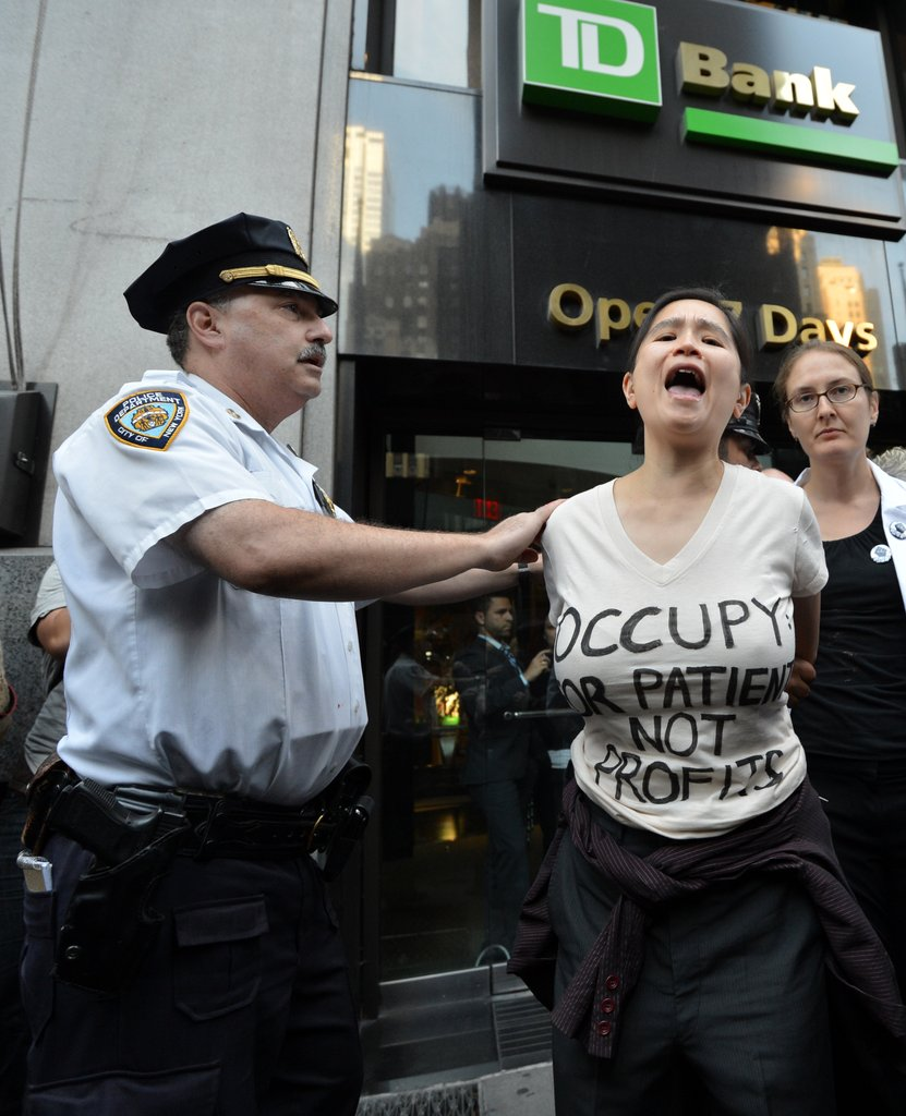 A female protestor was cuffed outside of a bank in NYC.
