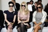 Dita Von Teese, Claudia Schiffer, and Victoria Beckham shielded their eyes while watching Roland Mouret in January 2008.