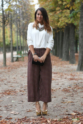 Whimsical dot pants, gold platforms, and statement jewels gave new life to a classic white blouse.