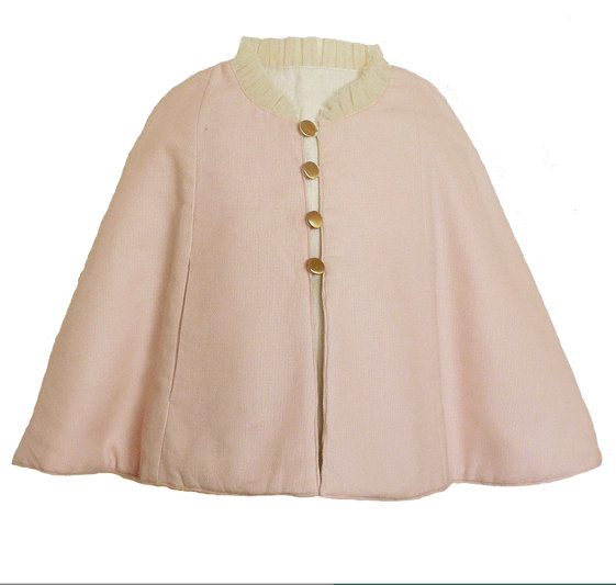 Rayil's reversible blush/ivory cape ($78) is made from basket-weave cotton with a tulle collar, self-seam pockets, and loop button closures.