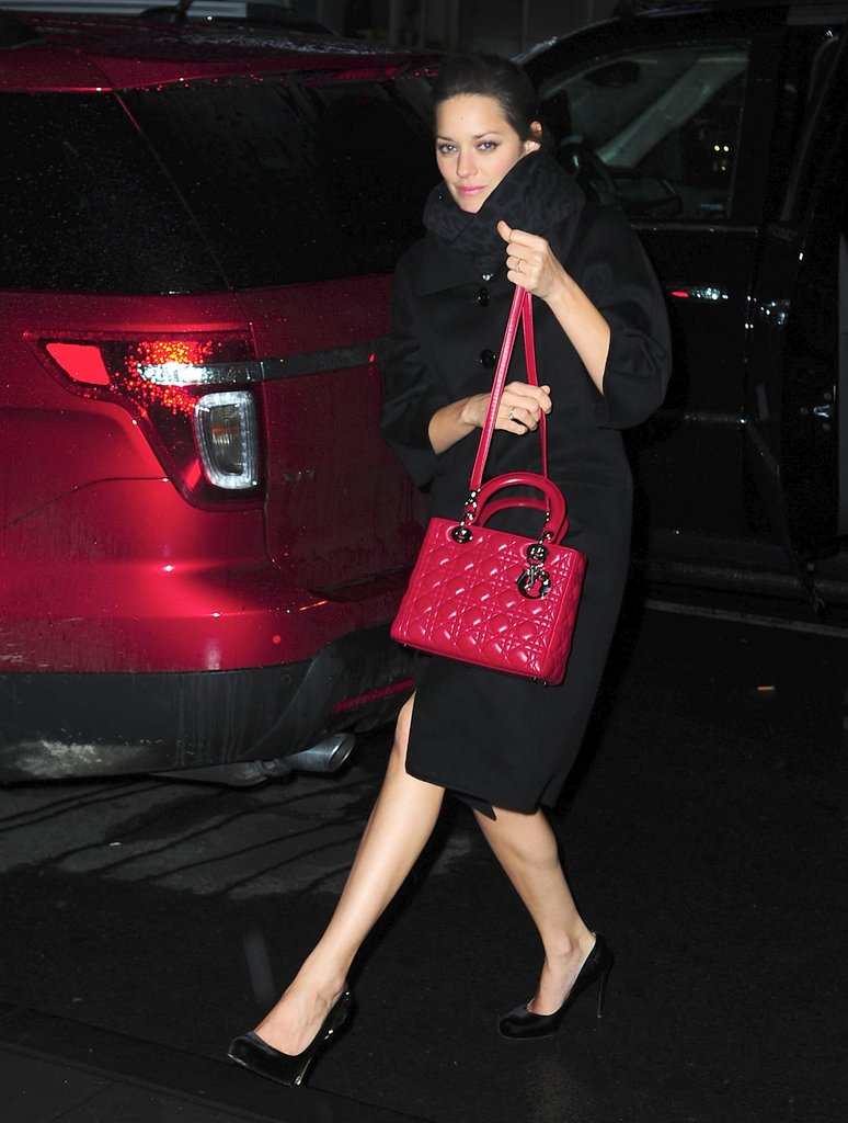 Marion Cotillard kept warm and simultaneously proved how chic outerwear can be — especially when accentuated with a berry-hued Dior bag.