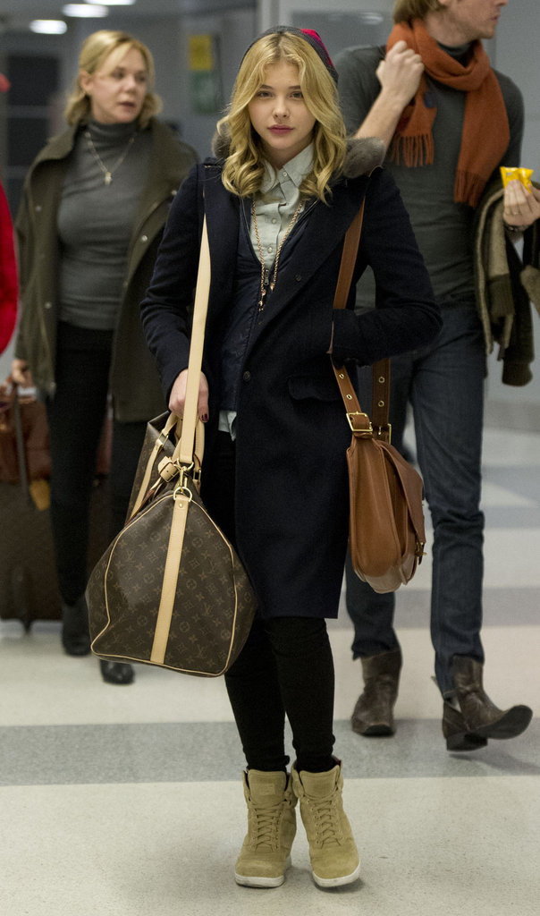 Louis Vuitton luggage adds a luxe twist to Chloë Grace Moretz's comfortable and casual look.