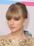 Playing with her hair and makeup at the 2012 American Music Awards, Taylor opted for a straight-hair updo and went for a bronzed smoky eye and soft pink lipstick.