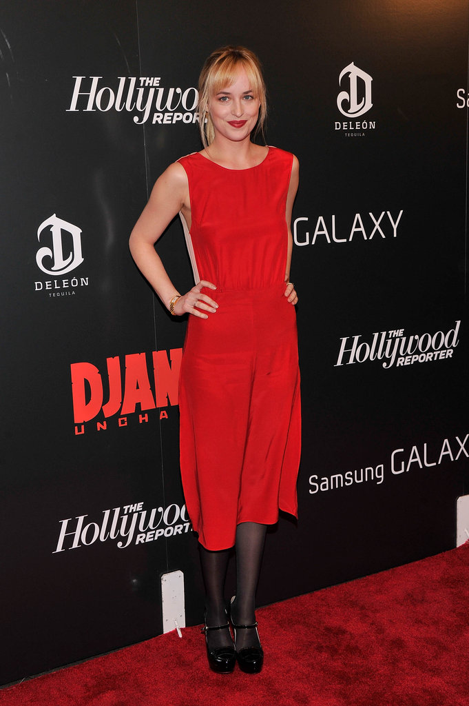 Dakota Johnson added a festive element to the evening in a red silk dress paired with ankle-strap sandals and a bold lip.
