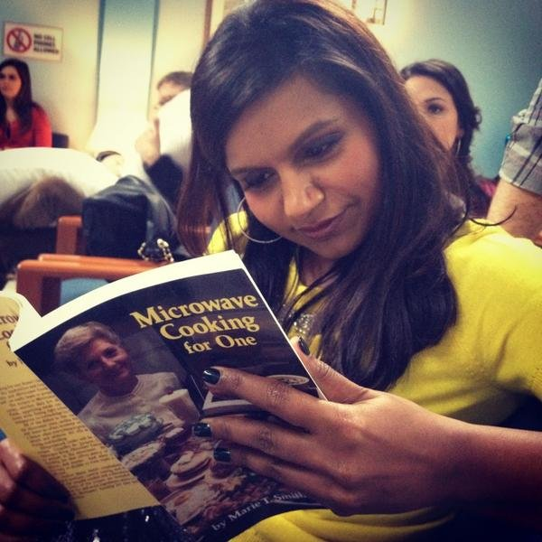 "Mindy Kaling leafed through the ""world's saddest and funniest prop"" on the set of The Mindy Project. Source: Twitter user mindykaling"
