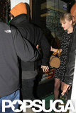 Harry Styles held onto Taylor Swift as they left a tattoo parlor together.