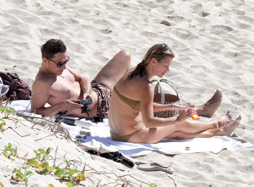 Kate Moss applies sunscreen to her legs.