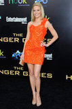 Elizabeth Banks stood out on the Hunger Games LA premiere red carpet, in large part to her bright orange Atelier Versace minidress.