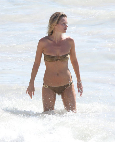 Kate Moss hit the waves in a golden little bikini with gilded hardware for added glam.