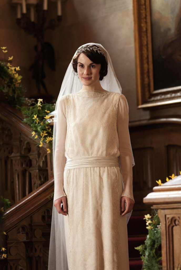 Mary looks elegant in her '20s-style wedding dress. The long-sleeved cream gown features rice pearls and Swarovski crystals and took eight weeks to create. Source: PBS