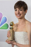Anne Hathaway smiled with her Golden Globe.