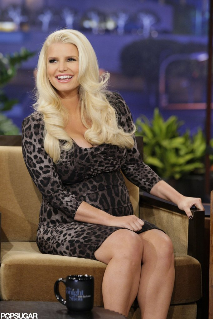 "Pregnant Jessica Simpson wore a low-cut dress for an appearance on The Tonight Show, during which she said she and fiancé Eric Johnson ""had two different wedding dates, but he keeps knocking me up!"""
