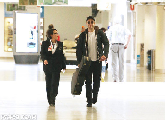 Robert Pattinson was escorted through the airport with his guitar.