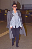 Pregnancy is bringing out Kim Kardashian's sleek and menswear-inspired side, according to this chic airport look. She took on the coat-draped-over-the-shoulders look with ease, letting the oxford shirt, navy trousers, and black peep-toe booties do the talking.