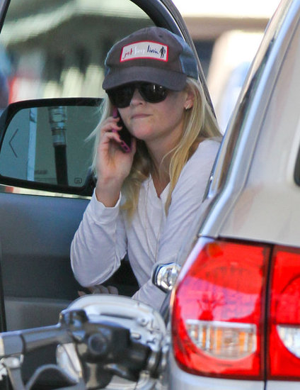 Reese Witherspoon talked on her cell phone while pumping gas at a local station.