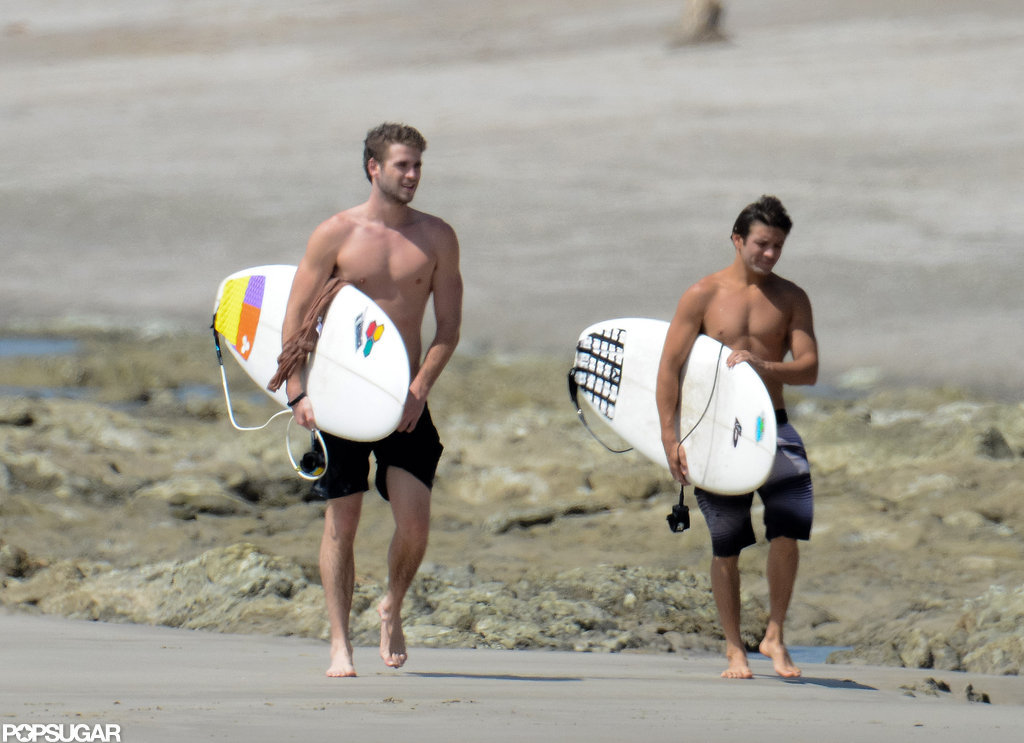 Liam Hemsworth walked on the beach with a friend.