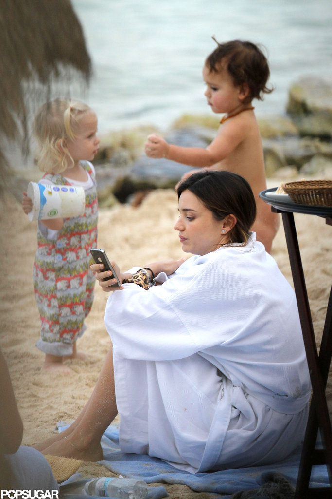 Flynn played in the sand as mom Miranda Kerr checked her phone.