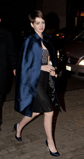 Anne Hathaway went dramatic in an Altuzarra dress with a brocade bodice and black skirt topped with a sapphire silk Burberry cape and matching pumps at a Les Misérables afterparty in London. Sparkling jewels and a mirrored clutch finished off her party style.