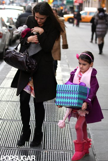 Suri Cruise carried a large present.