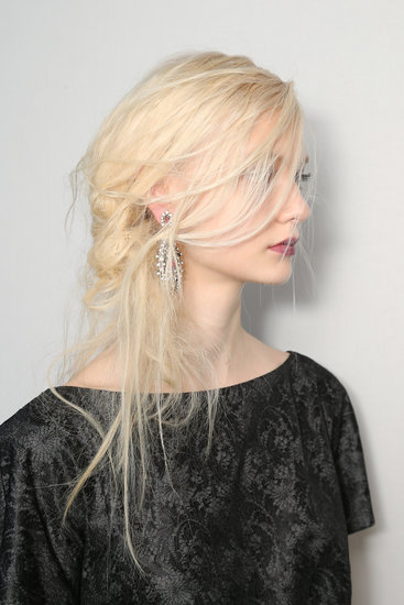 "Rodney Cutler for the Salon at Ulta Beauty created the windblown hairstyle. ""It's slightly romantic with a bit of gothic texture,"" he explained. Tadashi Shoji wanted the hair low on the neck, so Cutler created a ""knot"" of ""intertwining hair"" that was swept over one shoulder."