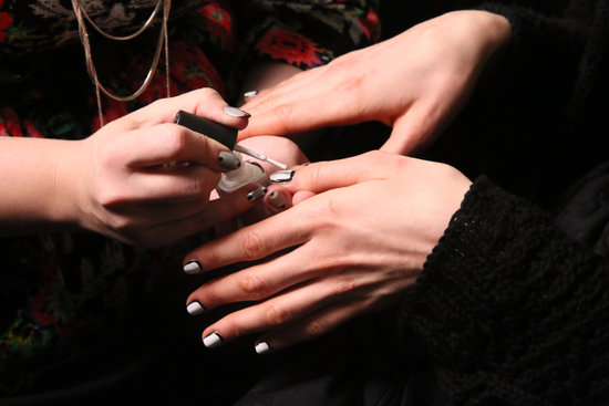 "The nails were designed by Simcha Whitehill for Color Club. She brought to life a ""picture frame"" manicure for a simple and graphic result.  To create the look, she painted the base color first (in this case, the black shade first). Then she painted the center white, leaving the perimeter black."