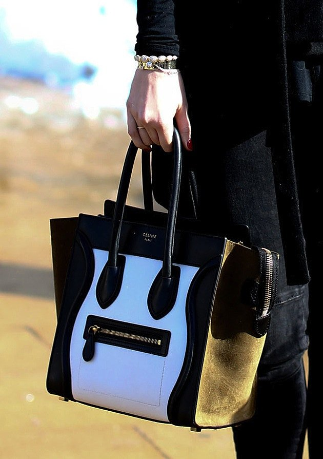 A two-toned Céline bag contrasts against a black ensemble.