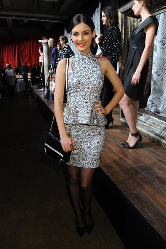 Victoria Justice sported a floral-print high-neck peplum dress with sheer tights at Alice + Olivia.