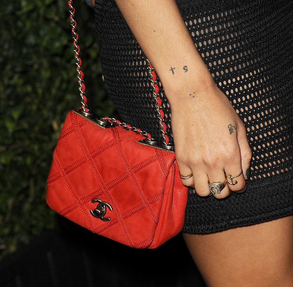 Providing a bit of color to her dark ensemble, Zoe chose an iconic red Chanel chain-strap bag to counter the black mini.