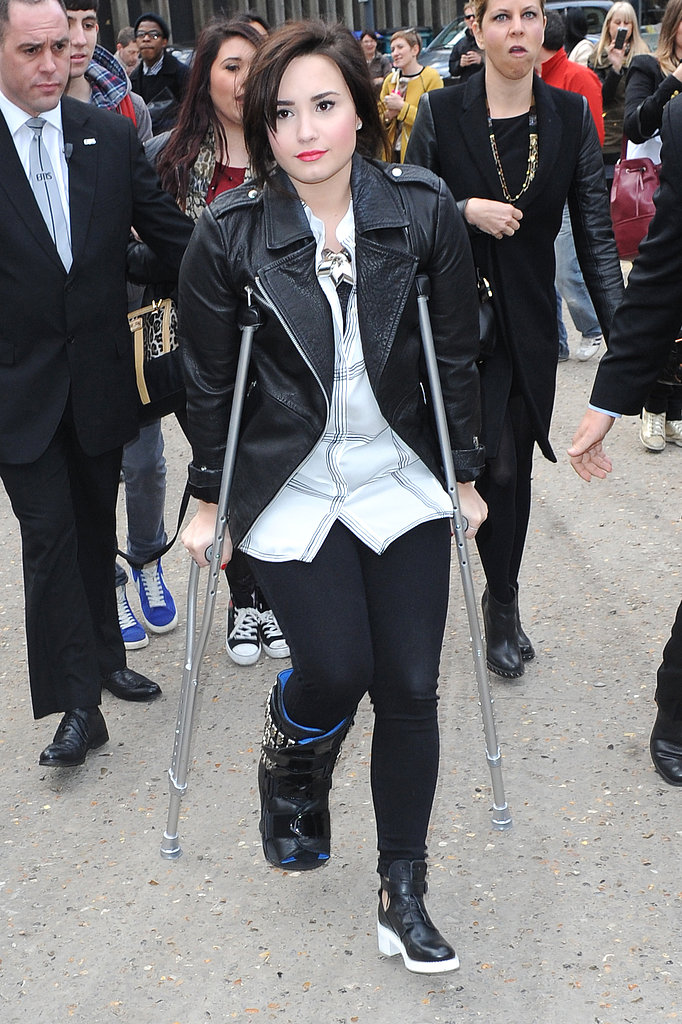 Demi Lovato was still stuck in a cast when she arrived at London Fashion Week in February.